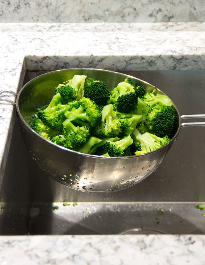 blanched broccoli florets draining in a colander