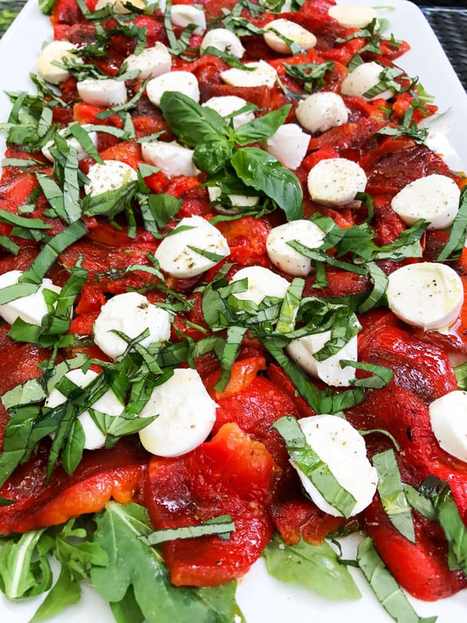 a platter of roasted red peppers with arugula and mozzarella cheese