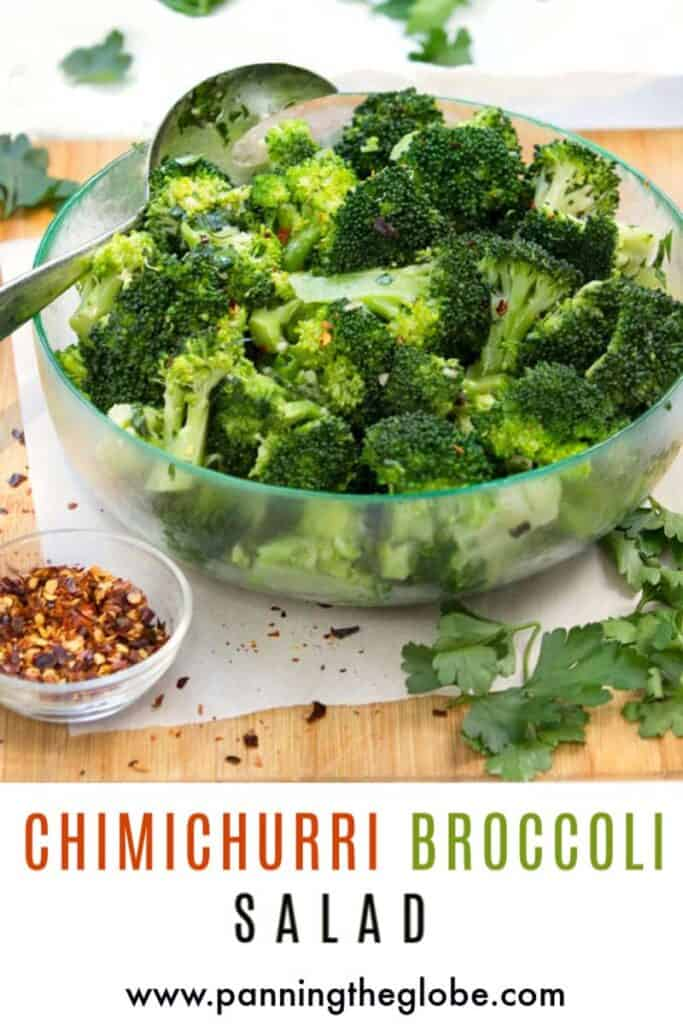Chimichurri broccoli salad in a clear bowl with a small bowl of red pepper flakes next to it