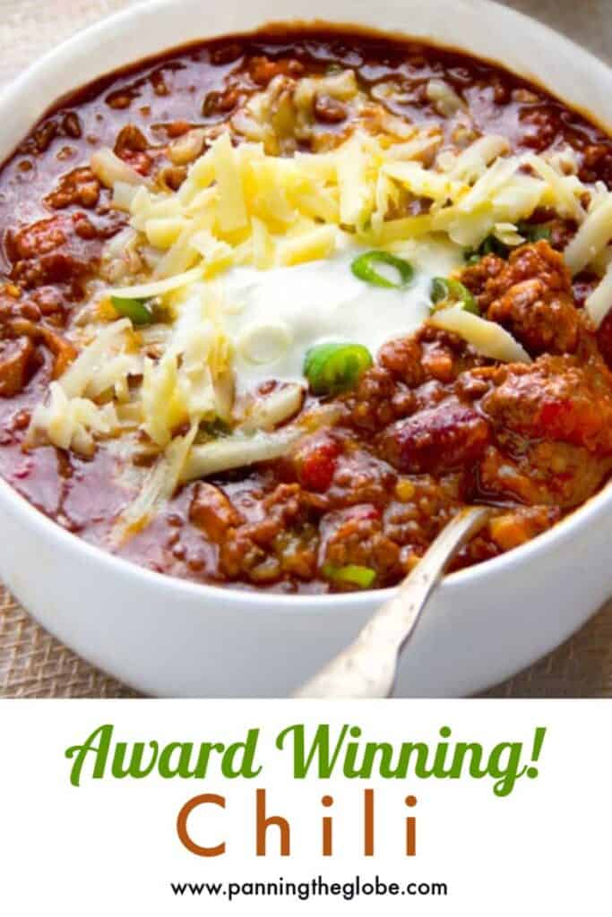 Pinterest pin: white bowl filled with chili con carne with a garnish of shredded cheddar, sour cream and chopped scallions