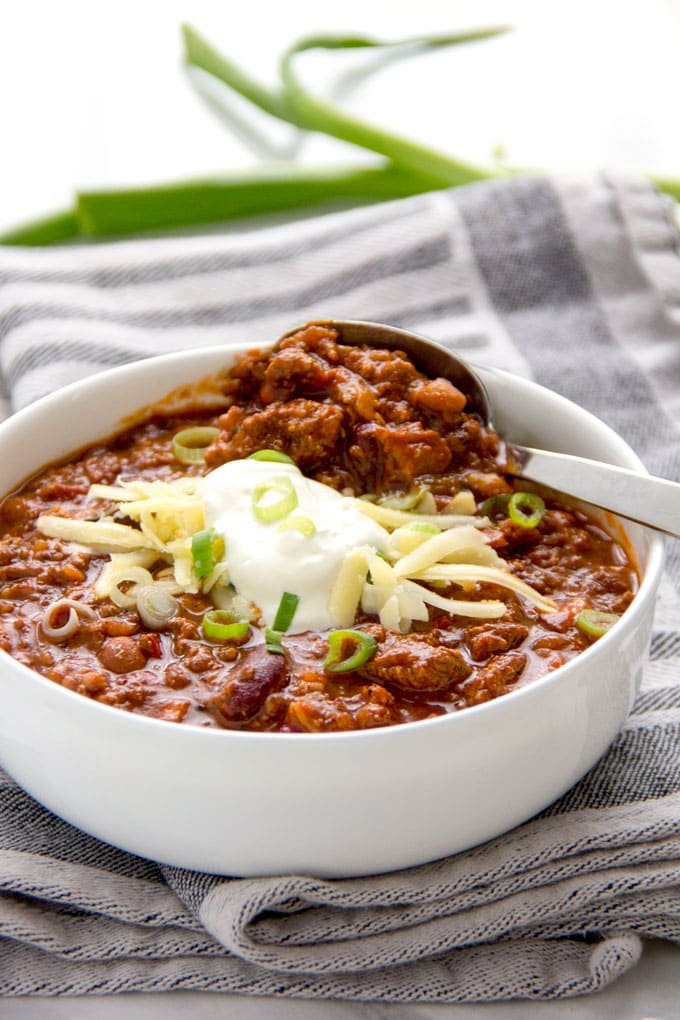 a bowl of award winning chili con carne with toppings