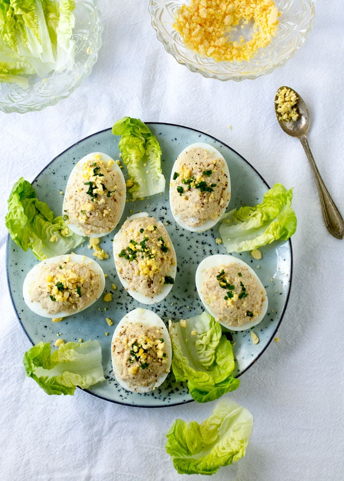 6 French Deviled Eggs Mimosa on a light blue plate, decorated with small lettuce leaves.
