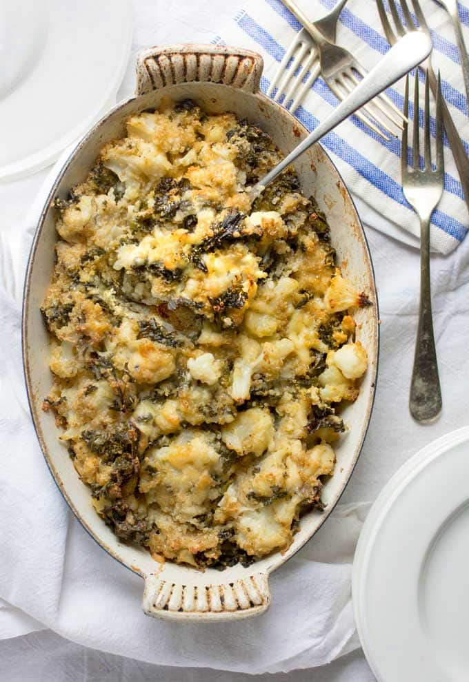 a casserole filled with cheesy cauliflower kale quinoa casserole, with lots of forks next to it on a blue and white striped napkin