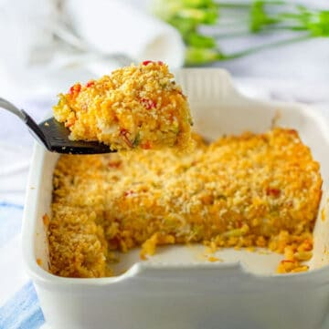 funeral potatoes in a white casserole dish with a large scoop of it on a spatula that is help up above the casserole dish