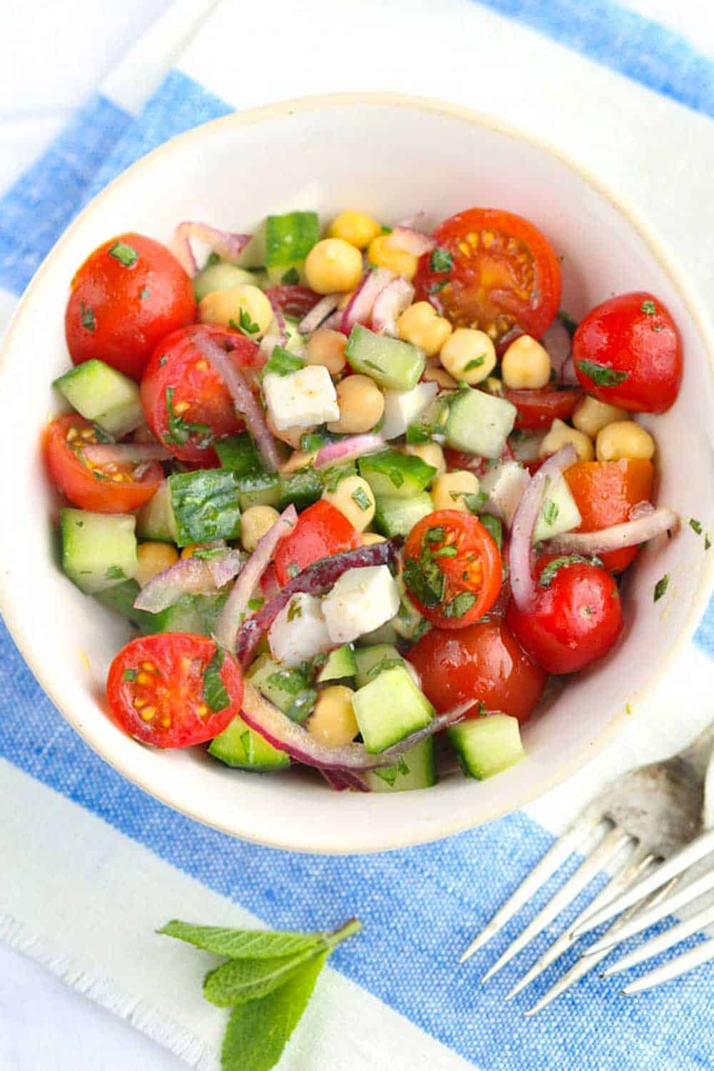 Mediterranean chickpea salad with cucumbers, feta, cherry tomatoes, herbs and lemony dressing