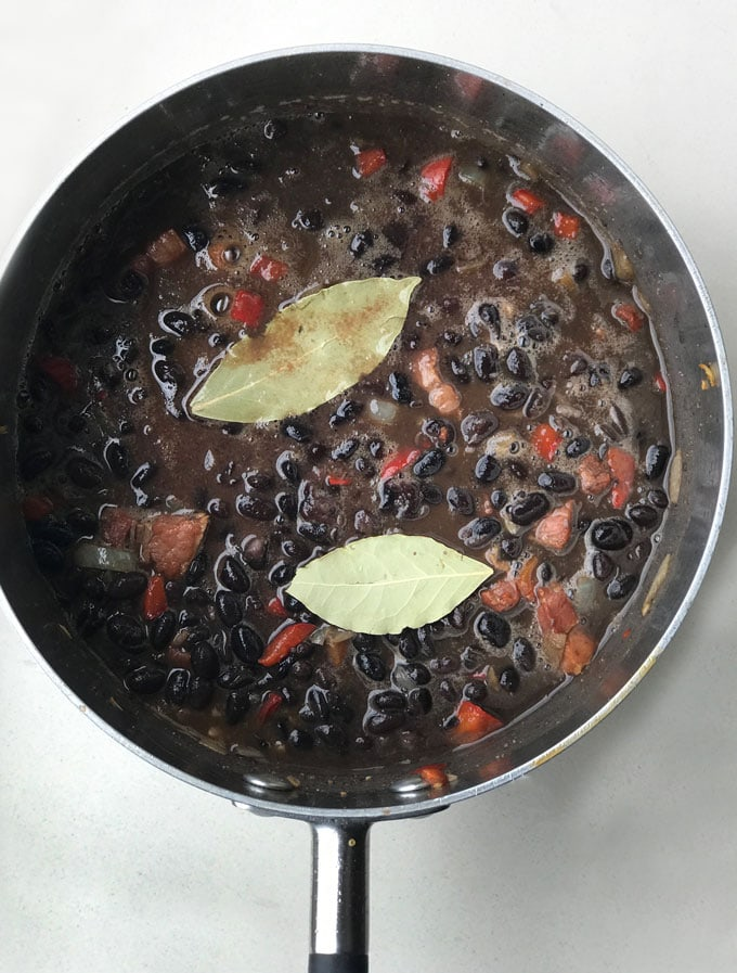 A pot of Cuban black beans with a couple of bay leaves on top.