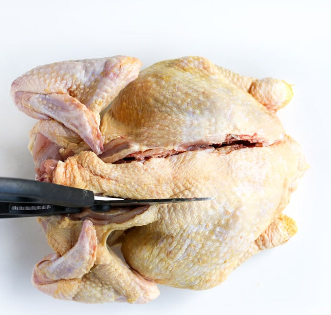 Cutting the backbone out of a whole chicken to butterfly it