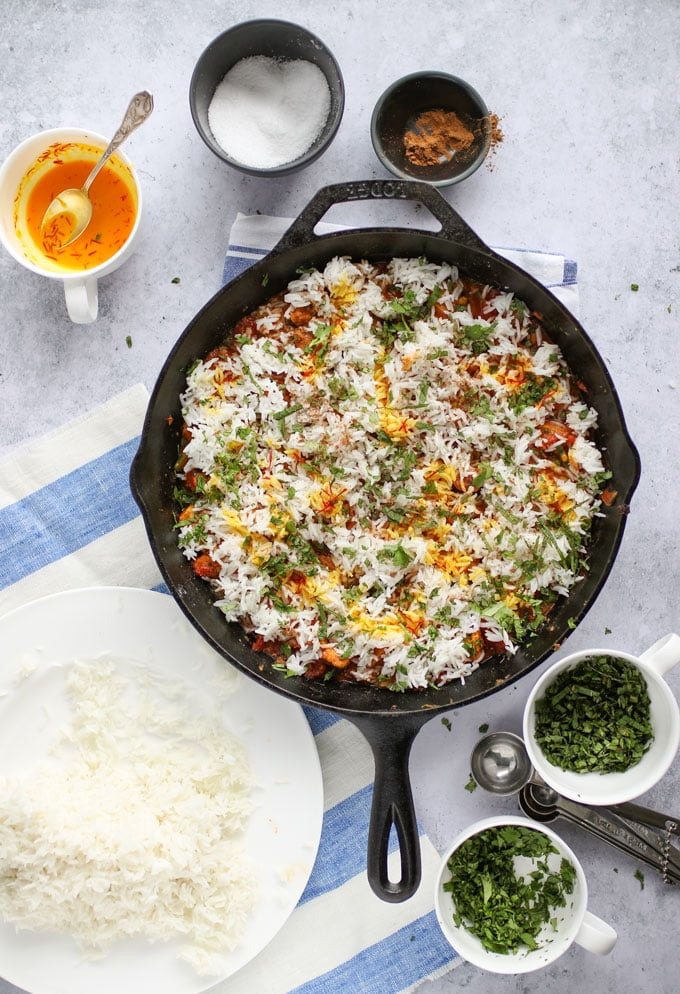 how to assemble chicken biryani in a skillet with rice, herbs, spices and saffron milk