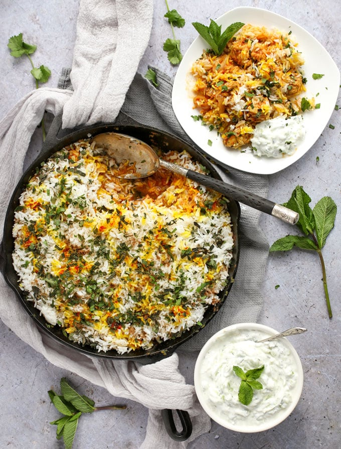 a skillet with chicken biryani and a plate of biryani with cucumber raita