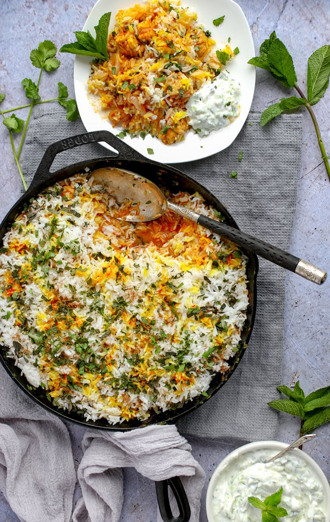 Skillet with Indian chicken biryani and a plate of biryani with a dollop of cucumber raita