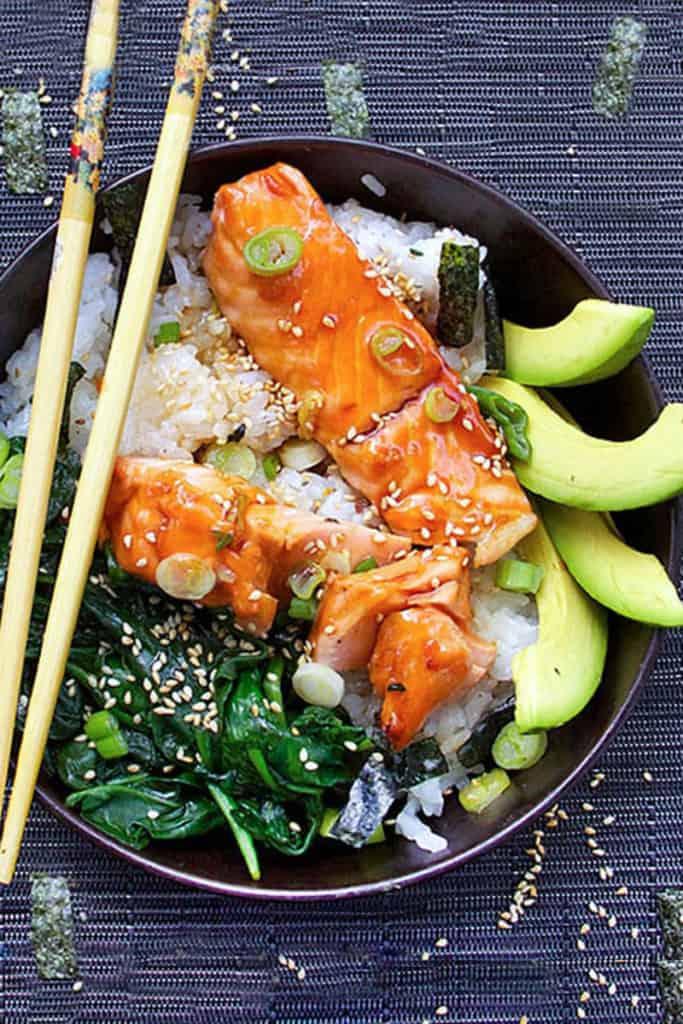 rice bowl with salmon teriyaki, sautéed spinach and sliced avocado, with chop sticks.