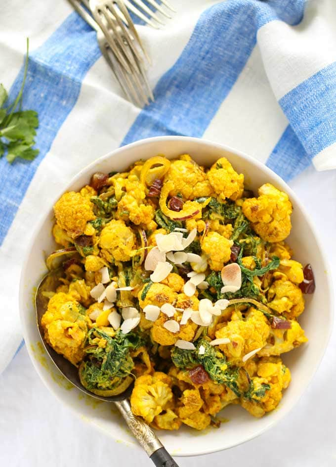A bowl of turmeric roasted cauliflower salad sprinkled with almonds