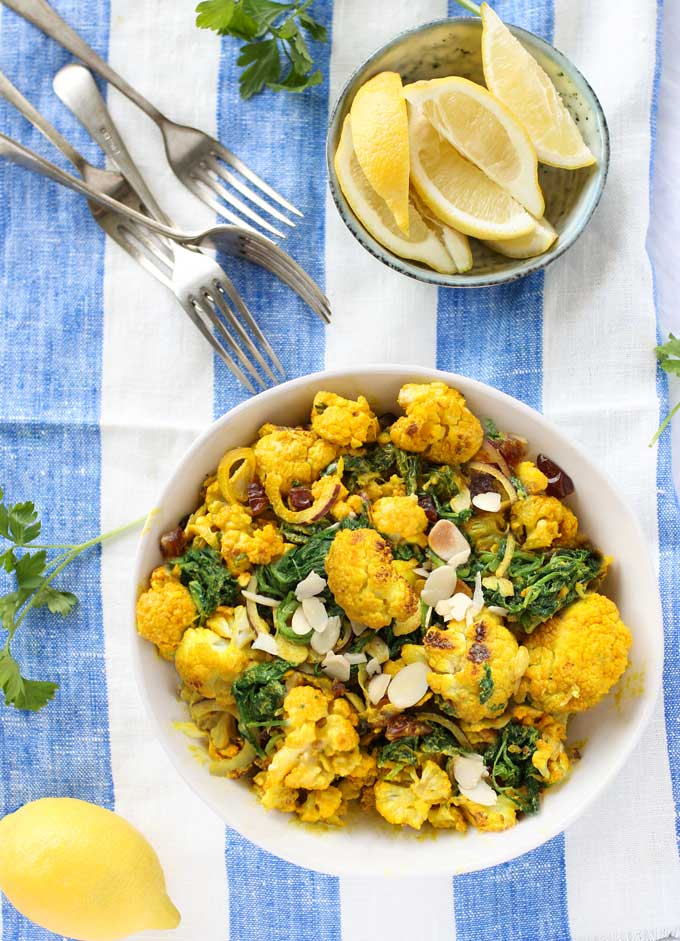 A bowl of turmeric roasted cauliflower salad and a bowl of lemon slices and forks