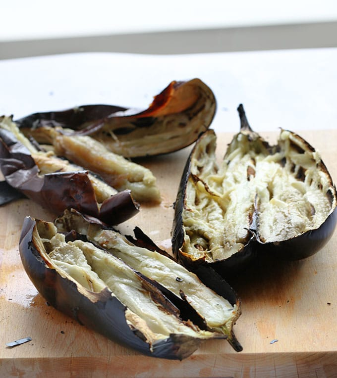 burnt eggplants cut open on a cutting board, ready to scoop into a bowl to make baba ganoush