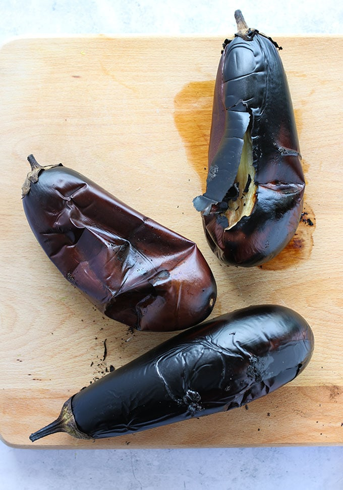 burnt eggplants on a cutting board, ready to make baba ganoush