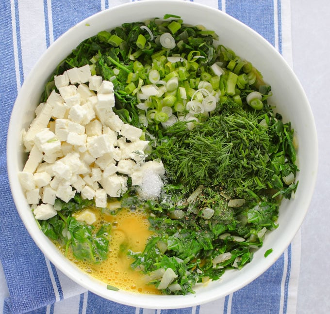 a bowl with the filling ingredients for Greek spinach pie with potato crust