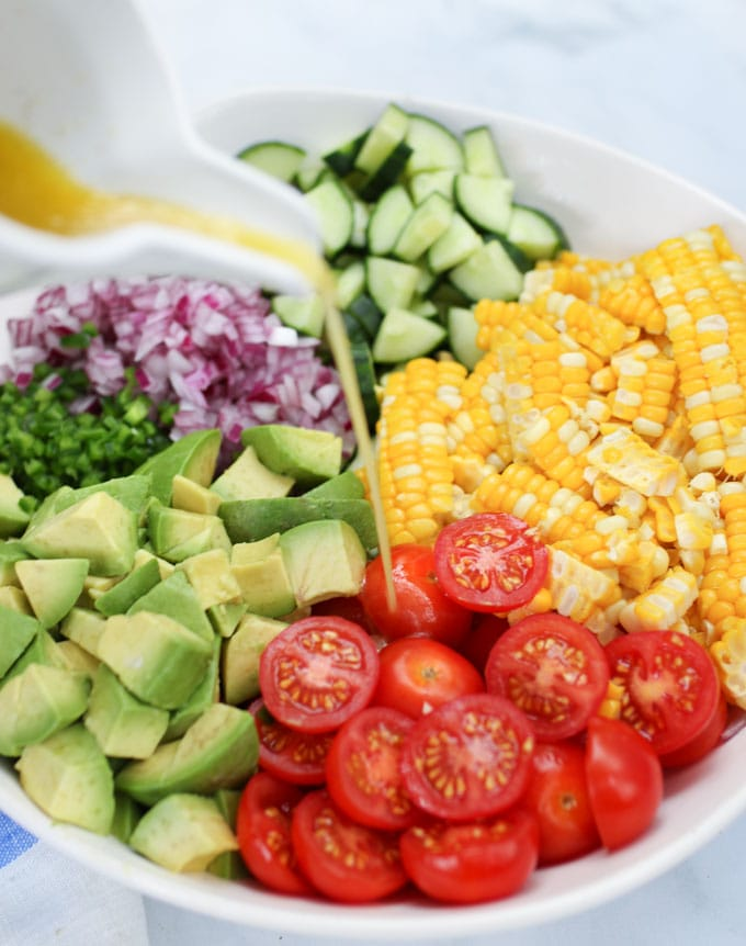Pouring dressing on ingredients for corn, tomato, avocado salad