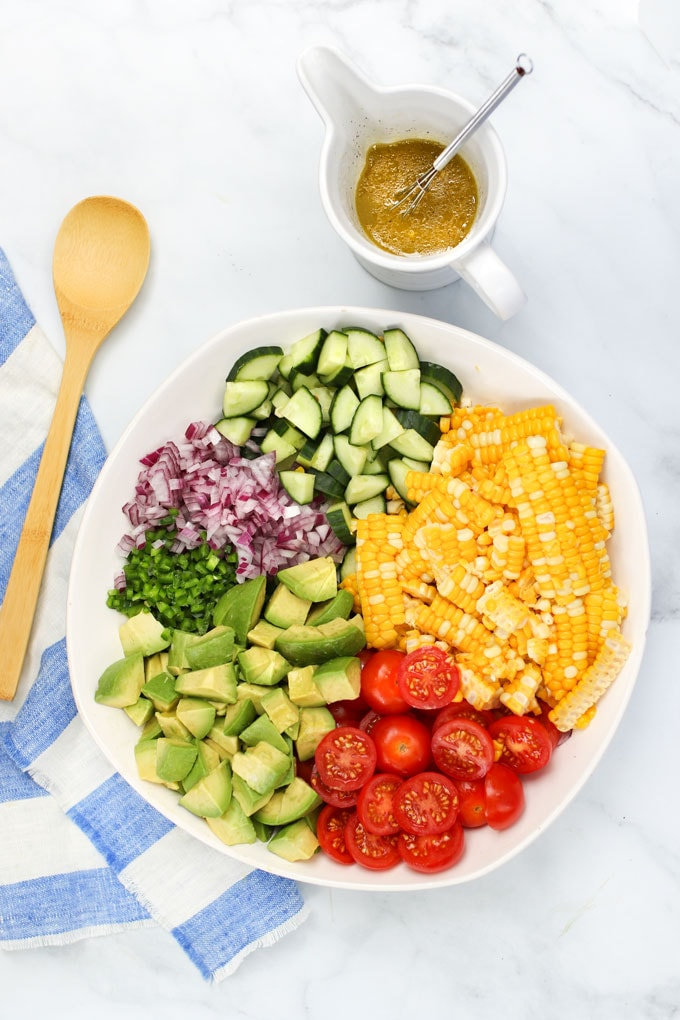 Ingredients for corn tomato avocado salad: Dressing plus a bowl with corn kernels, cubed avocado, sliced cucumbers, halved cherry tomatoes, chopped red onion and jalapeno peppers.