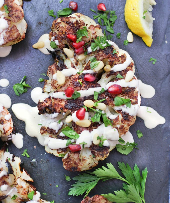 Grilled cauliflower shawarma with lemony tahini sauce, pine nuts and pomegranate seeds