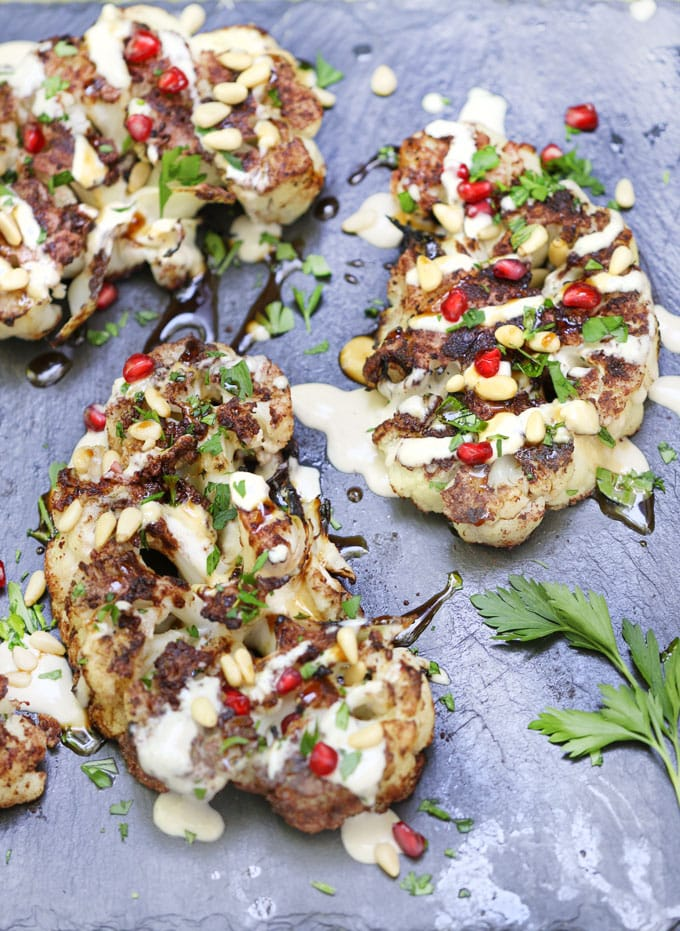 Cauliflower shawarma steaks on a platter with tahini and pomegranate seeds
