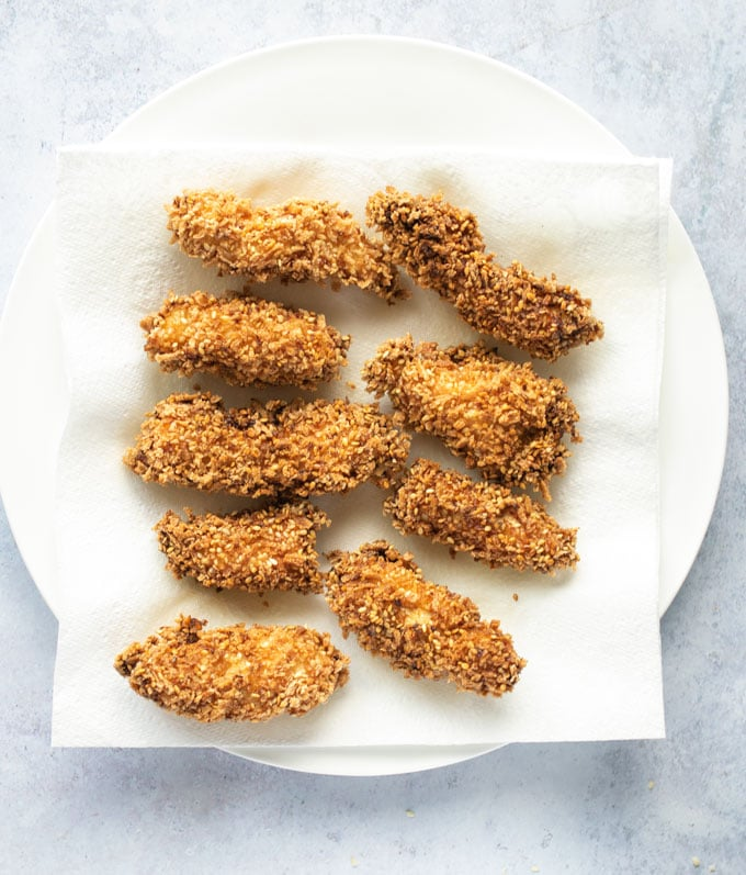 fried chicken bites draining on paper towel lined plate