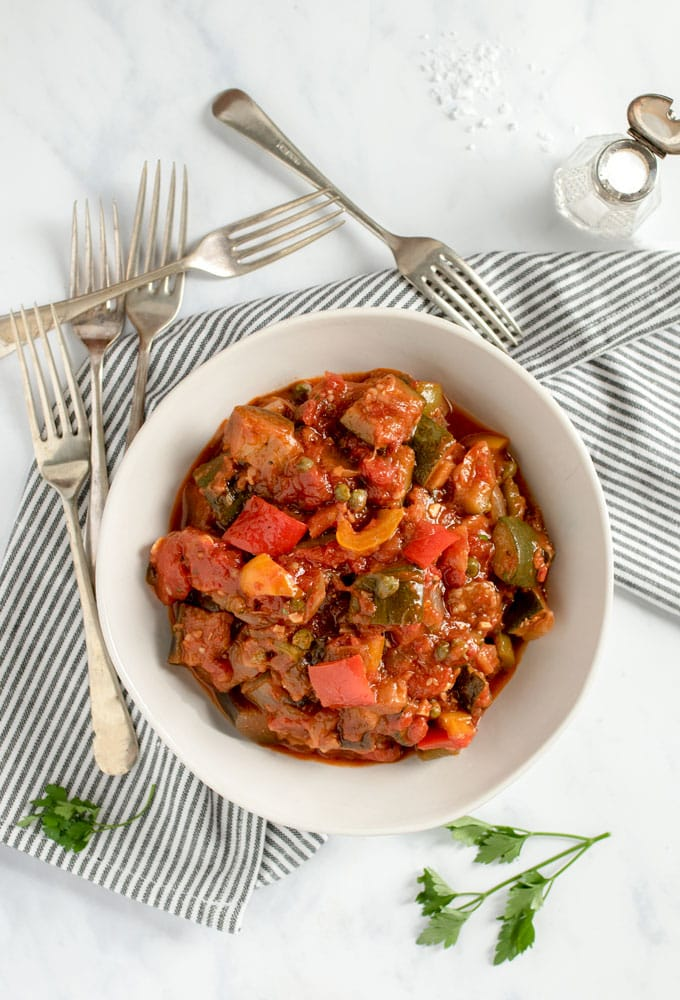 A bowl of ratatouille with lots of forks around it