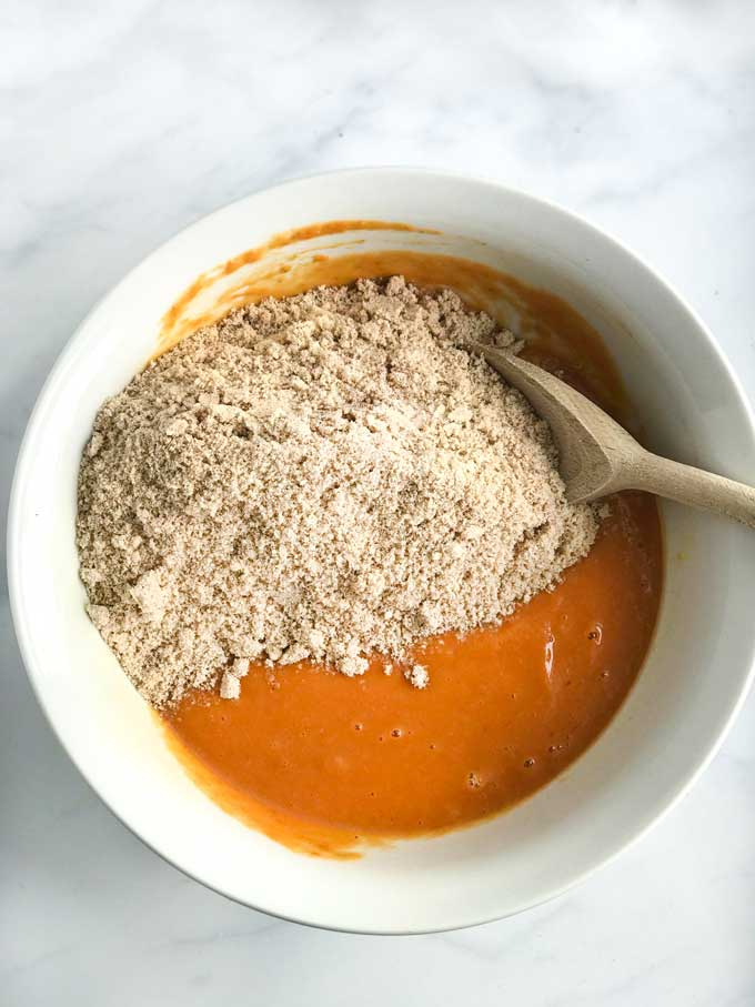 A bowl with ingredients for making healthy pumpkin bread with almond flour