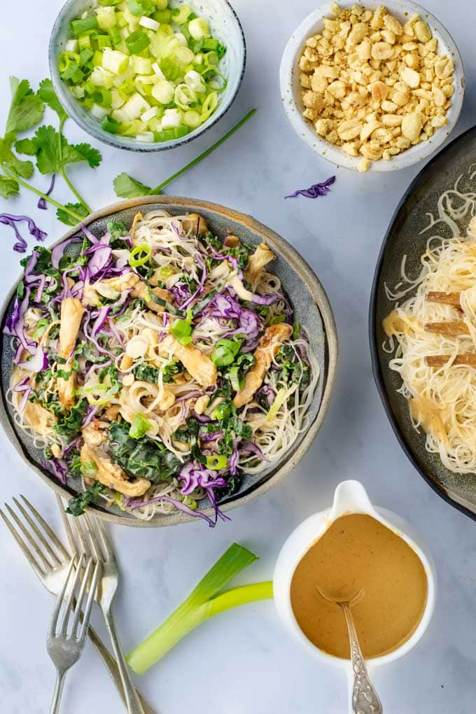 Thai Noodle salad bowl with peanut sauce and little bowls of peanuts and scallions