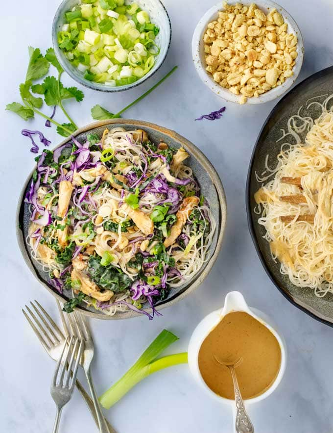 Thai Noodle Salad bowl surrounded by bowls of peanut dressing, chopped peanuts and chopped scallions