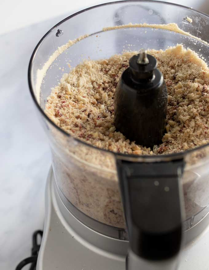 Close up of the bowl of a food processor filed with ground dried fruits and nuts