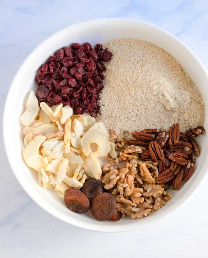 Big white bowl with dried cranberries, dried apple slices, almond flour, walnuts, pecans and dried apricots
