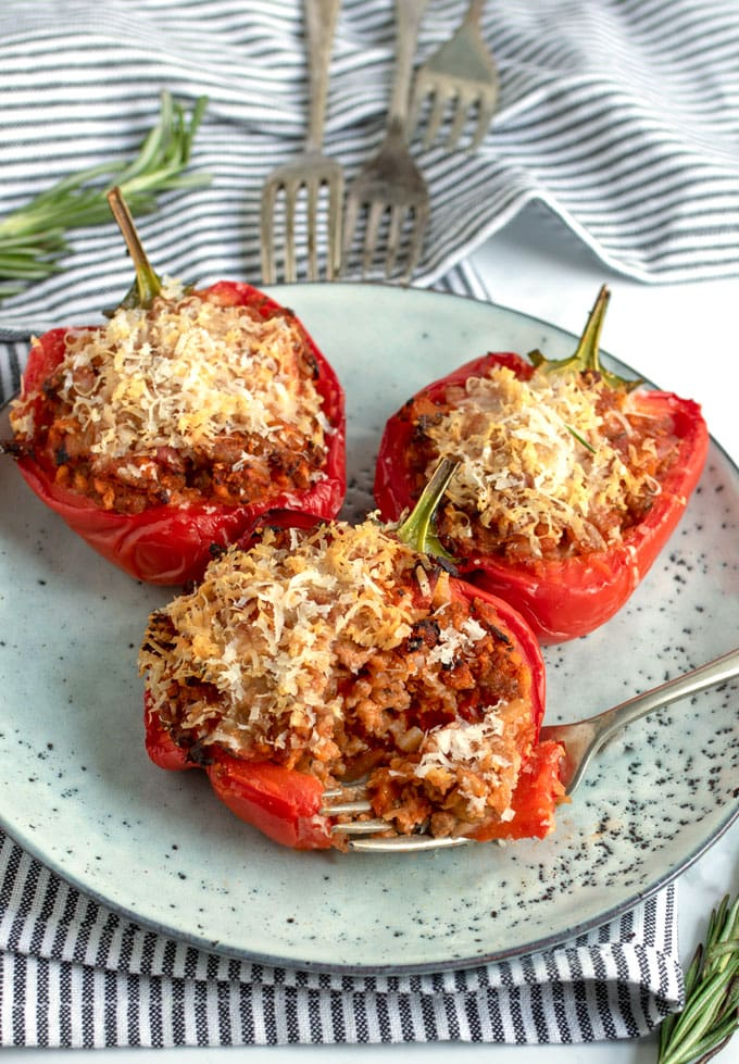 three pork and parmesan stuffed red peppers on a plate with three forks in the background and a sprig of rosemary and a striped dish towel
