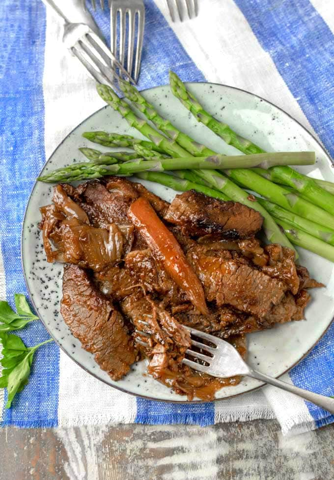 A plate of Nach Waxman's brisket with a carrot on top and asparagus on the side, with a blue and white striped cloth napkin and four forks