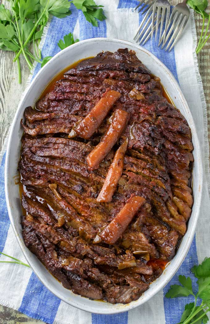 A serving dish with Nach Waxman's Brisket, cooked, sliced and topped with four cooked carrot pieces, on a blue and white striped napkin garnished with parsley and forks
