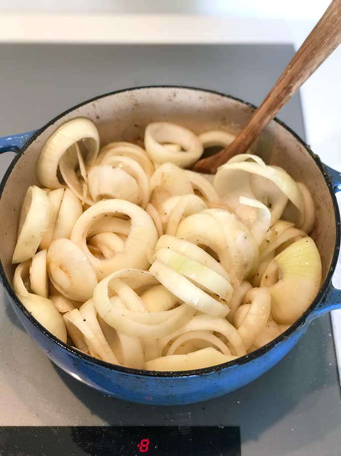 Blue Dutch oven filled to the brim with thickly sliced rings of raw onions