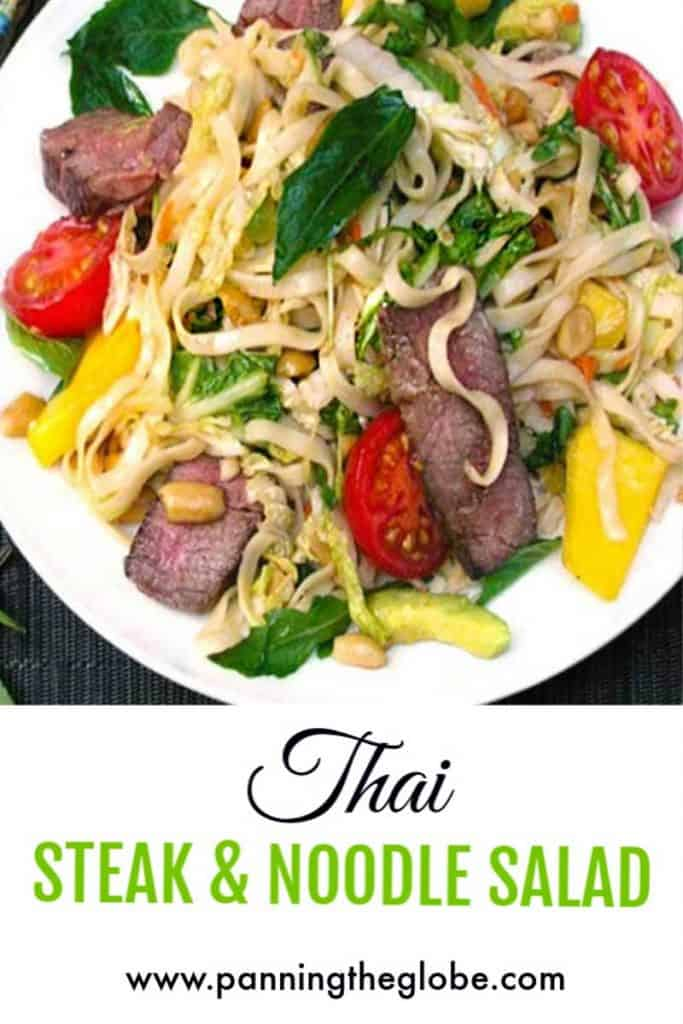 White plate filled with Thai steak and noodle salad, 2 pieces of sliced steak, swirly noodles, tomatoes, mangos and mint leaves