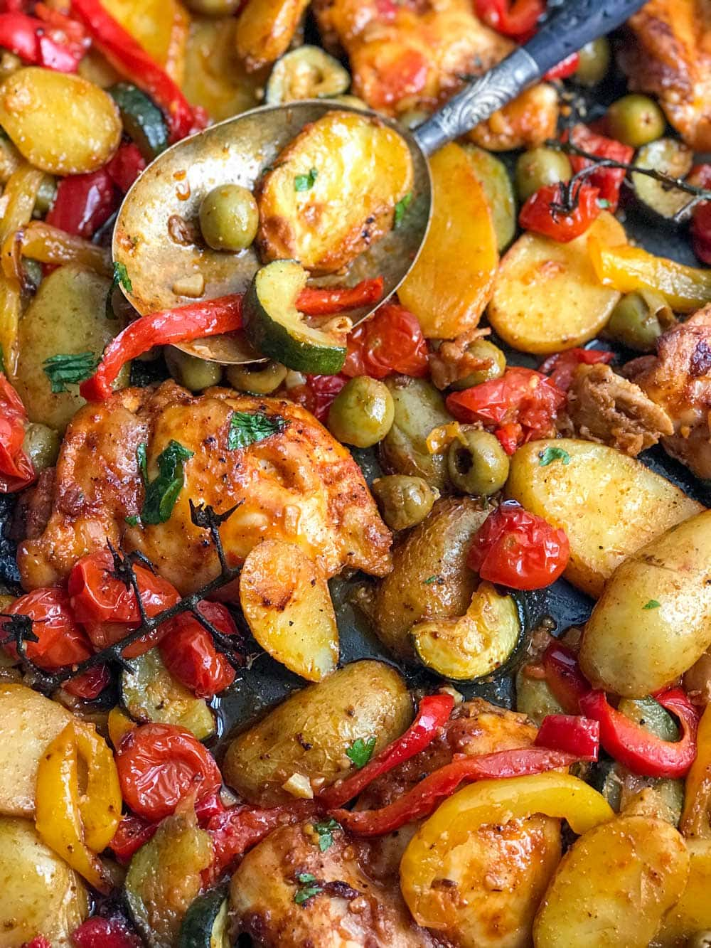 close up of a baking dish with baked boneless chicken thighs, sliced baby potatoes, red and yellow bell peppers, chunks of zucchini, green olives and cherry tomatoes.