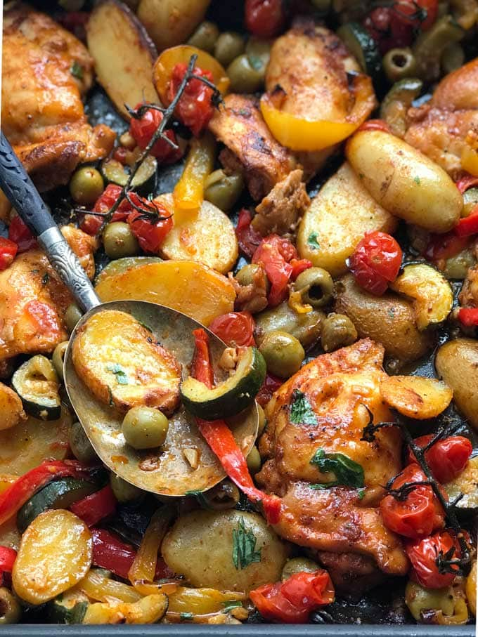 close up of a baking dish with a decorative serving spoon and baked boneless chicken thighs, sliced baby potatoes, red and yellow bell peppers, chunks of zucchini, green olives and cherry tomatoes.