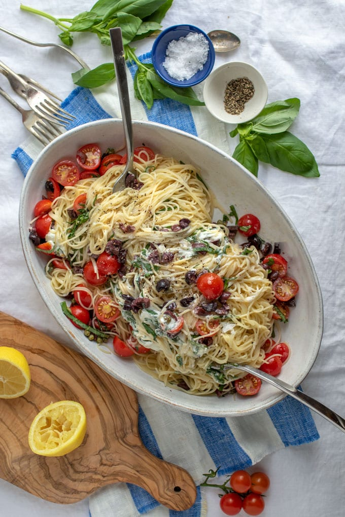 A white tablecloth spread with basil leaves, lemons on a cutting board, small bowls of salt and pepper, and an oval serving bowl filled with summer pasta of angel hair with goat cheese and fresh tomatoes