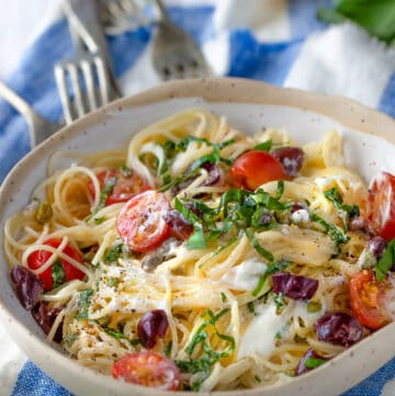 bowl of angel hair pasta with cherry tomatoes, goat cheese, basil and olives, on a blue and white striped dish towel with four forks pointing to the bowl and lemons in the background
