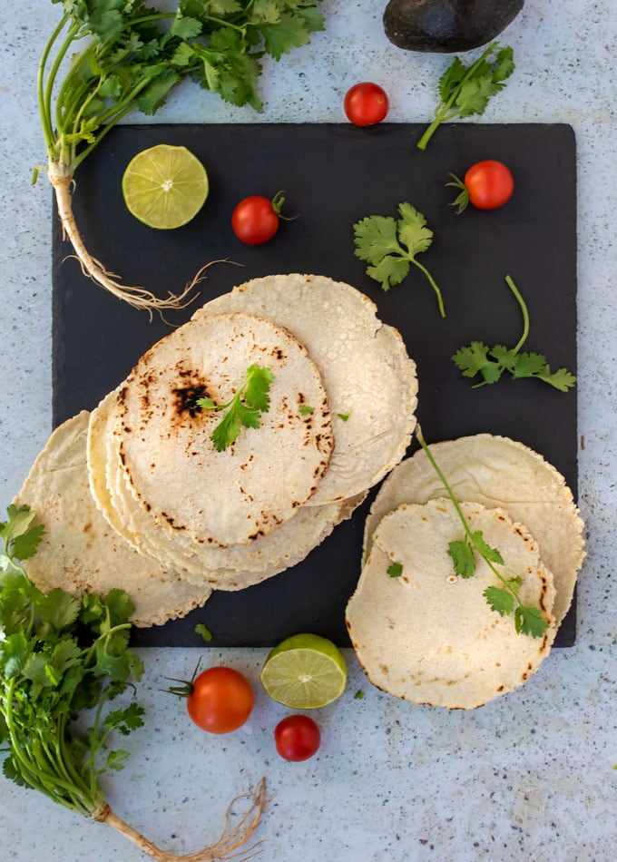 a stack on homemade corn tortillas on a black slate board, surrounded by sprigs of cilantro, cherry tomatoes and two lime halves