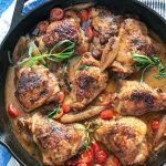 cast iron skillet with 8 braised chicken thighs in mustard wine sauce with sliced cherry tomatoes and sprigs of tarragon