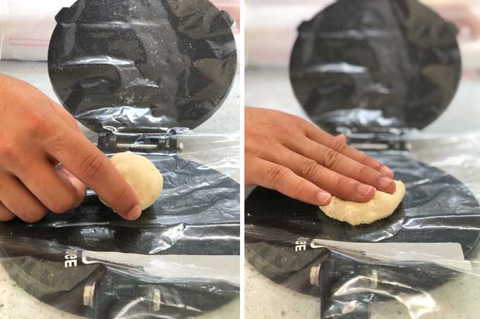 a hand placing a ball of dough in a tortilla press and pushing it down into the press