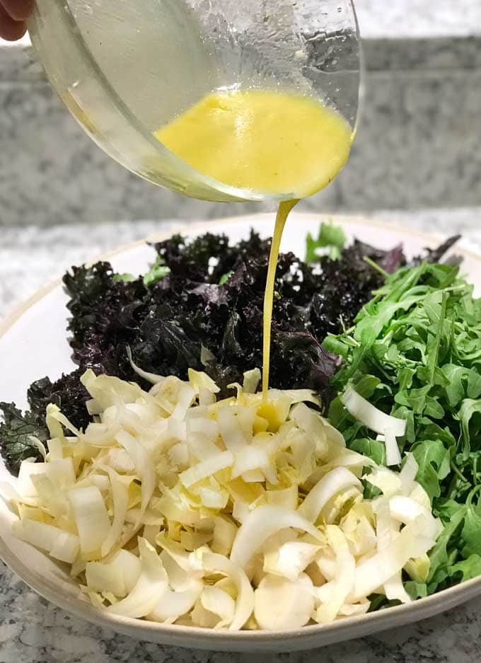 pouring lemon dijon vinaigrette into a bowl with three lettuces, kale, endive and arugula.