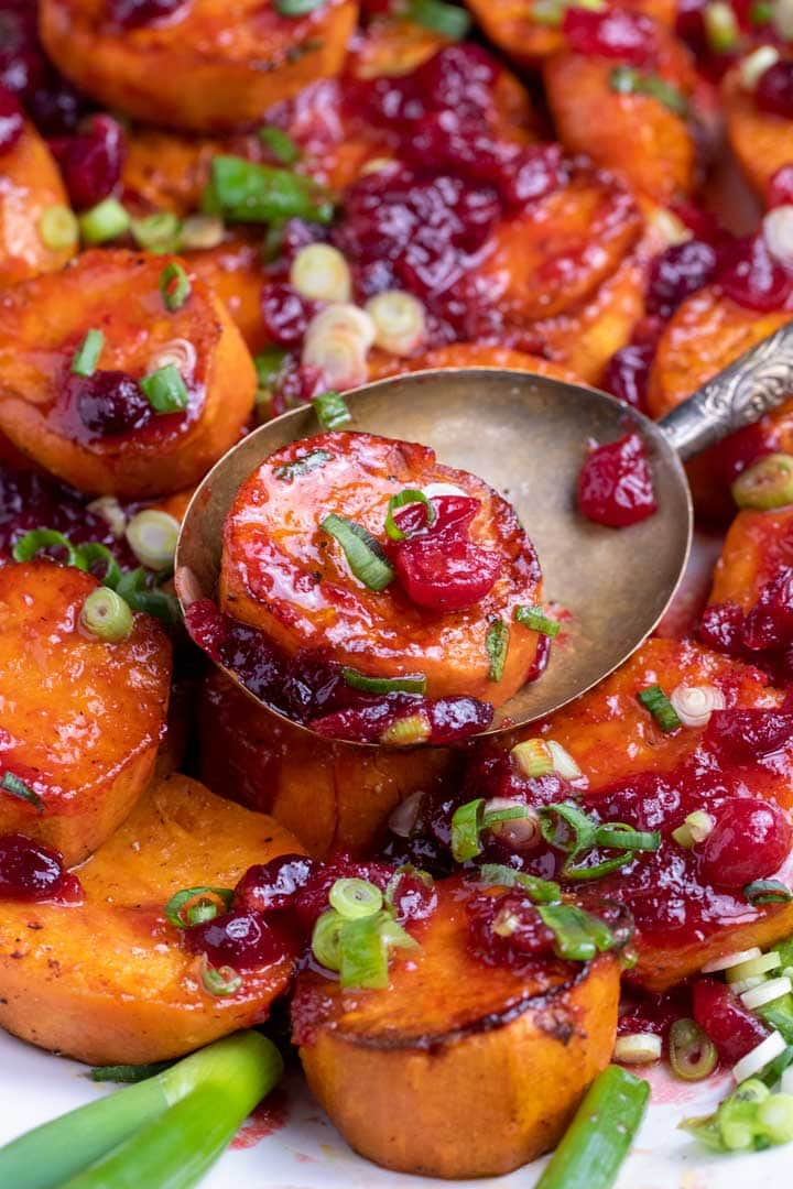 close up of roasted sweet potatoes with ruby red cranberry glaze and cranberries