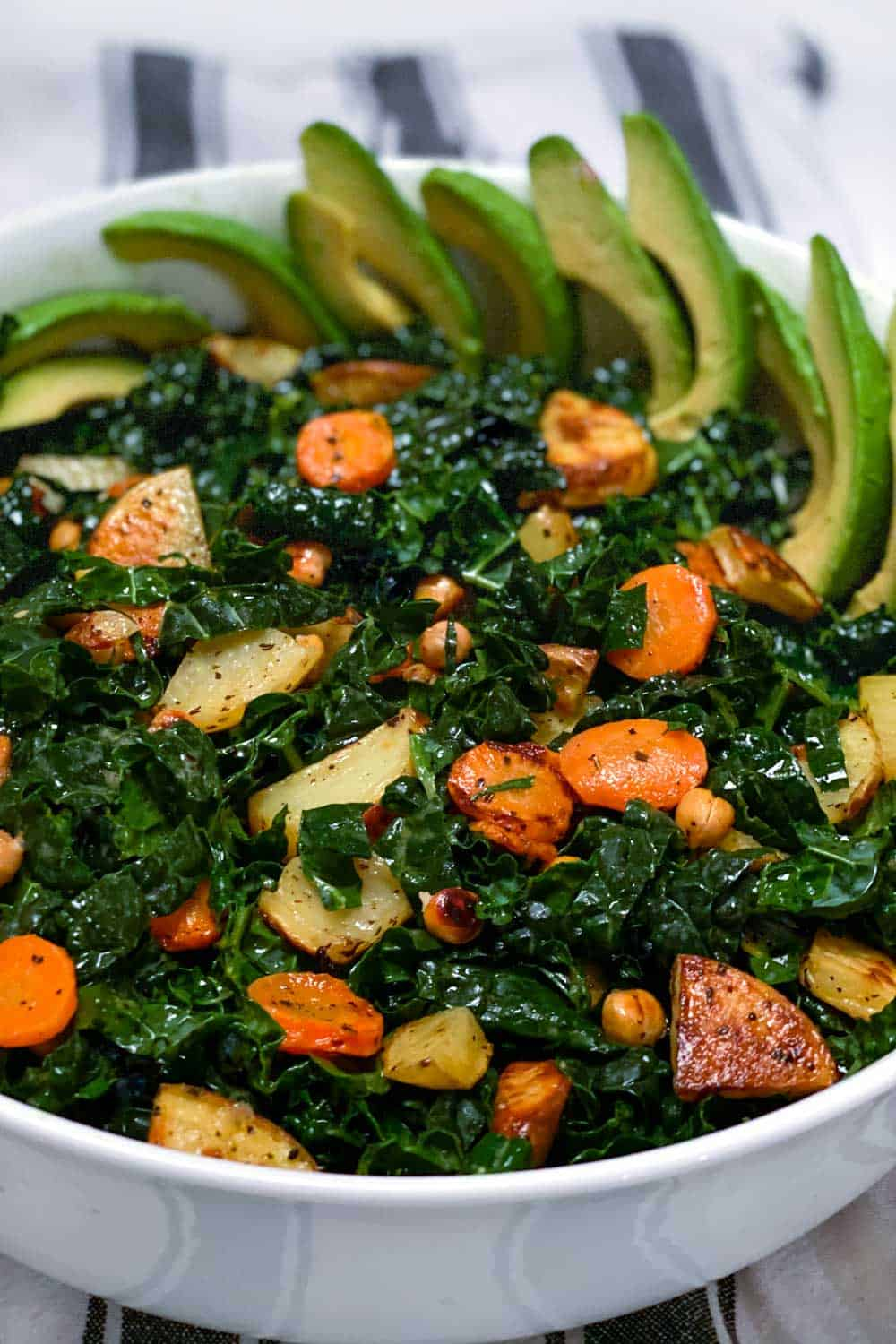 close up of white serving bowl filled with shredded kale and roasted carrots, potatoes, chickpeas and sliced avocado