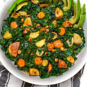 white serving bowl on black and white striped dish towel, filled with shredded kale and roasted carrots, potatoes, chickpeas and sliced avocado