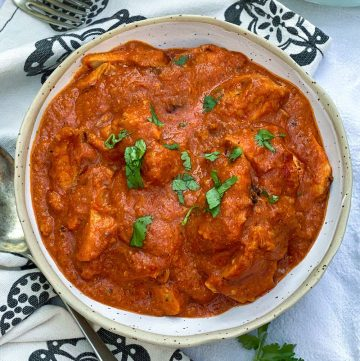 White bowl filled with Chicken Ruby, vibrant tomato-based Indian chicken curry, sprinkled with chopped cilantro