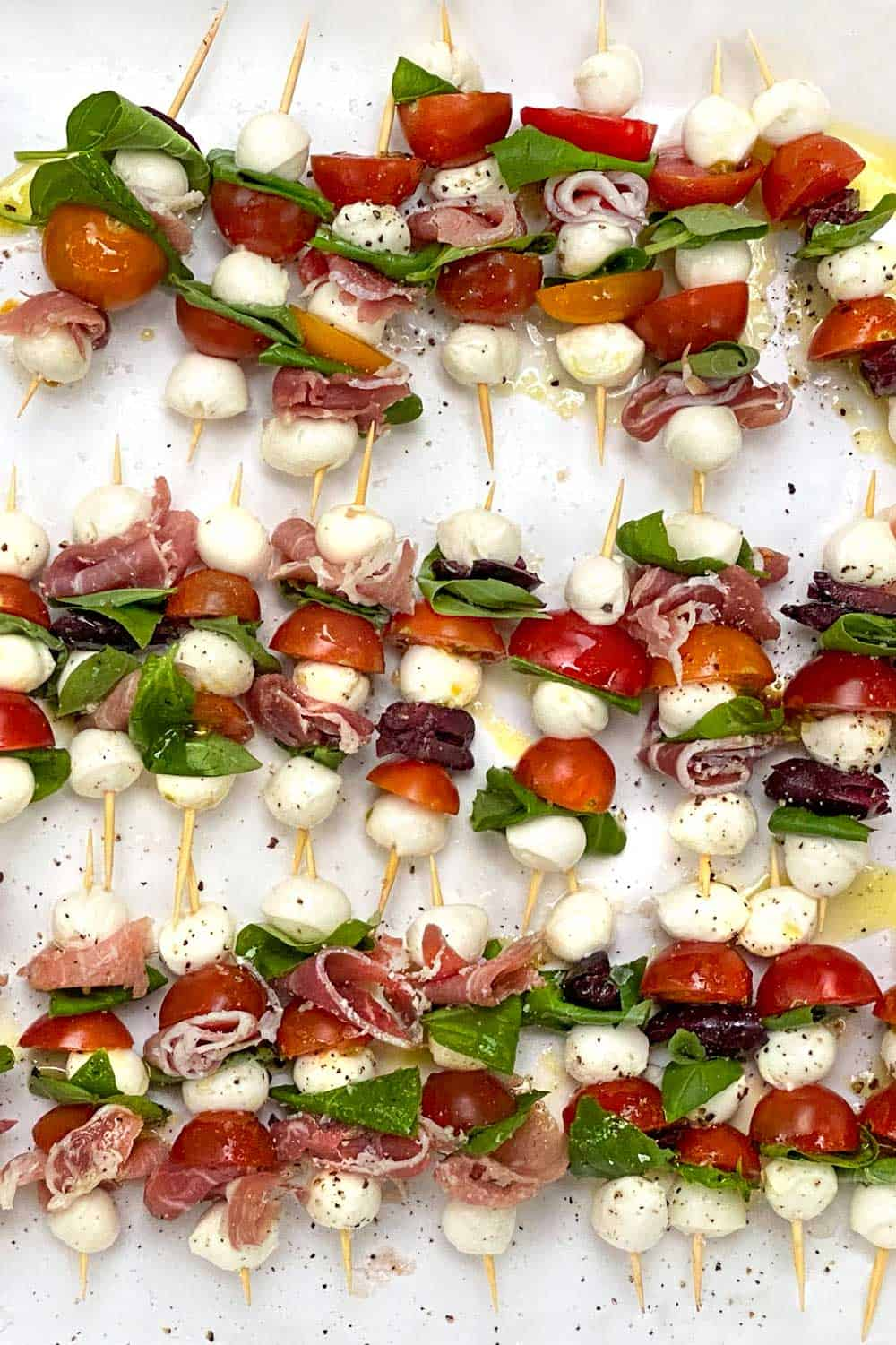 mini caprese skewers with mini mozzarella balls, cherry tomatoes and fresh basil leaves