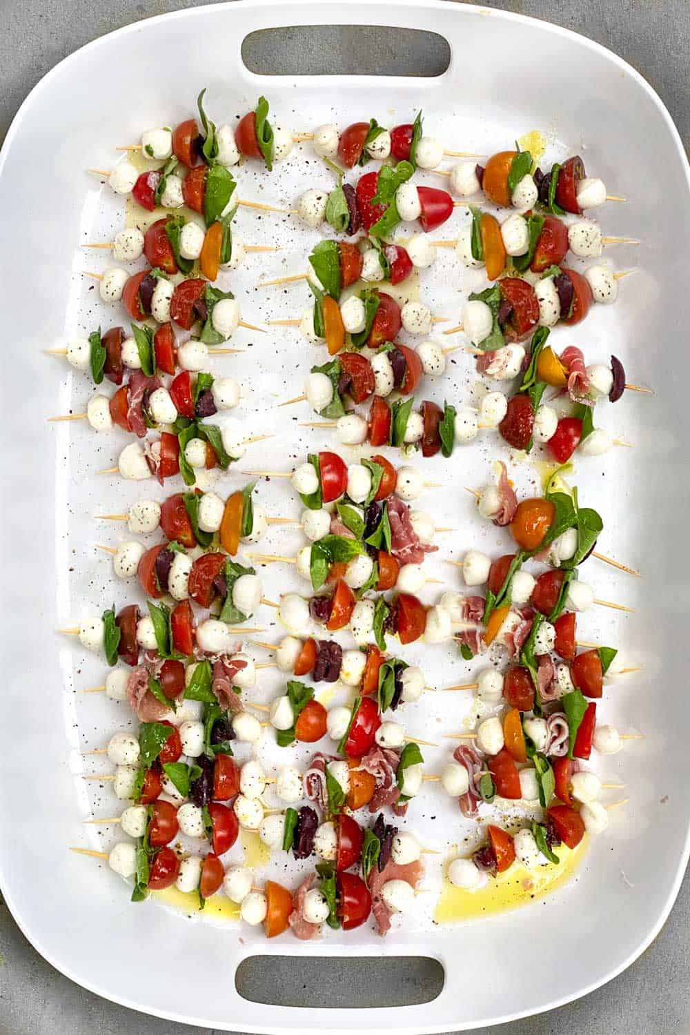3 dozen mini caprese skewers on a white tray, with tomatoes, basil leaves and mini mozzarella balls